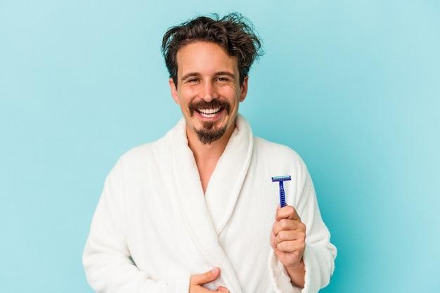 Giovane uomo caucasico che tiene una lama di rasoio isolata su sfondo blu ridendo e divertendosi.