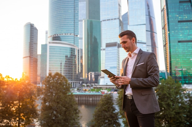 Giovane smartphone caucasico della tenuta dell'uomo per il lavoro di affari.