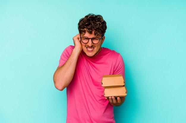 Giovane uomo caucasico che tiene due hamburger isolati su sfondo blu che copre le orecchie con le mani.