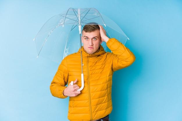Giovane uomo caucasico che tiene un ombrello scioccato