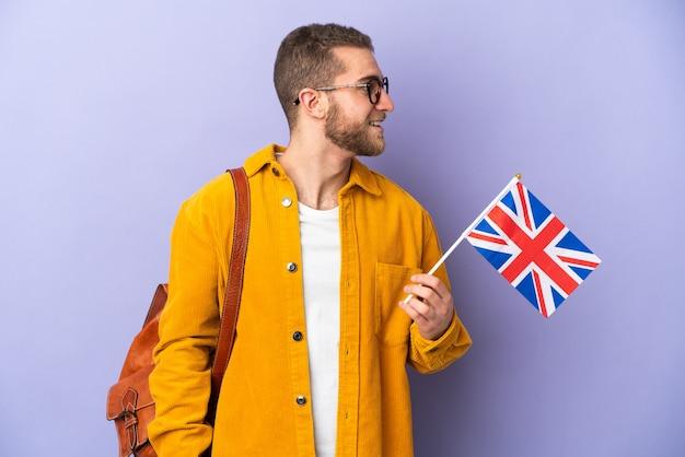Giovane uomo caucasico che tiene una bandiera del regno unito isolata sulla parete viola che osserva lato