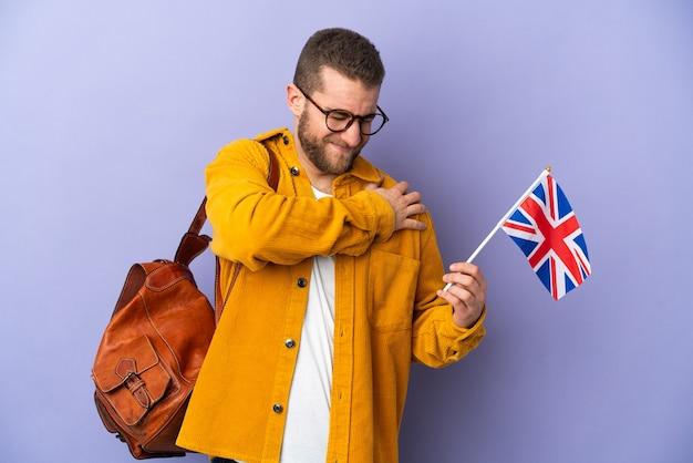 Giovane uomo caucasico che tiene una bandiera del regno unito isolata sul muro viola soffre di dolore alla spalla per aver fatto uno sforzo