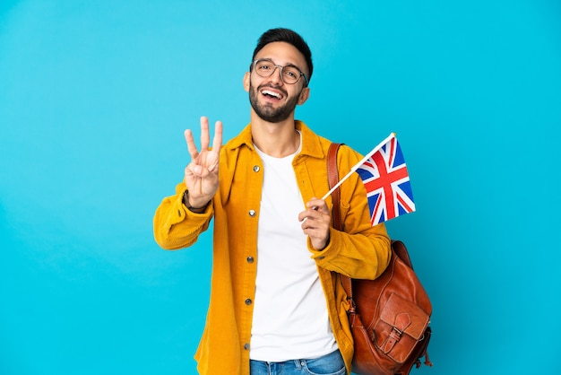 Giovane uomo caucasico che tiene una bandiera del regno unito isolata su sfondo giallo felice e contando tre con le dita