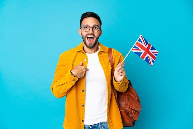Giovane uomo caucasico che tiene una bandiera del regno unito isolata su sfondo giallo con espressione facciale a sorpresa