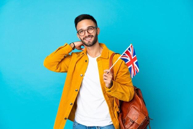 Giovane uomo caucasico che tiene una bandiera del regno unito isolata sulla risata gialla della parete