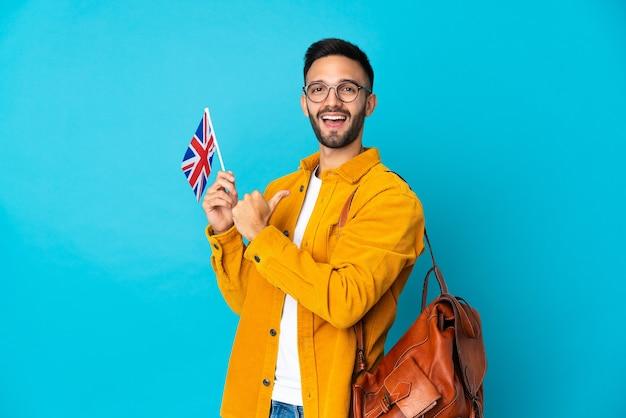 Giovane uomo caucasico che tiene una bandiera del regno unito isolata sul muro giallo orgoglioso e soddisfatto di sé