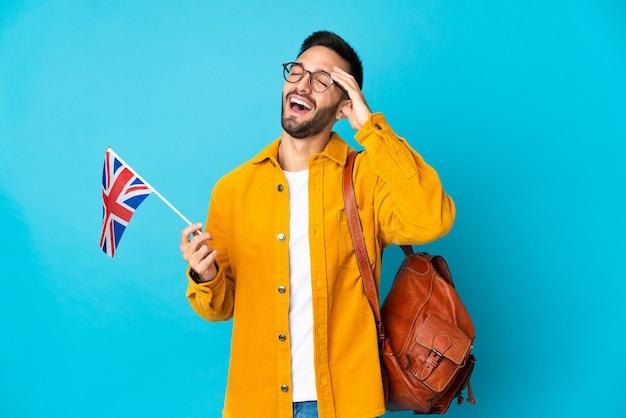 Giovane uomo caucasico che tiene una bandiera del regno unito isolata sulla parete gialla che sorride molto
