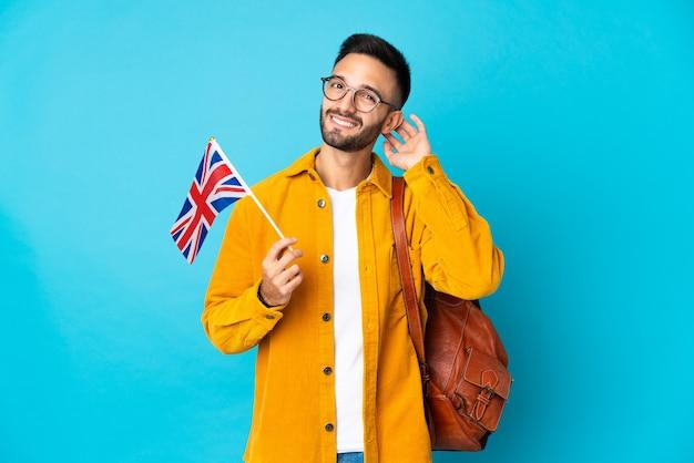 Giovane uomo caucasico che tiene una bandiera del regno unito isolata