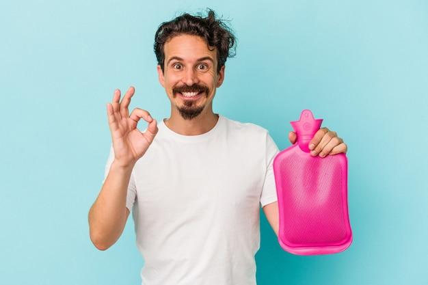 Giovane uomo caucasico che tiene una sacca d'acqua isolata su sfondo blu allegro e fiducioso che mostra gesto ok.