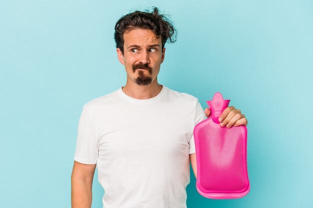 Il giovane uomo caucasico che tiene una sacca d'acqua isolata su sfondo blu confuso, si sente dubbioso e insicuro.