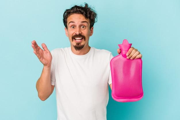 Giovane uomo caucasico che tiene una sacca d'acqua isolata su sfondo blu riceve una piacevole sorpresa, eccitato e alzando le mani.