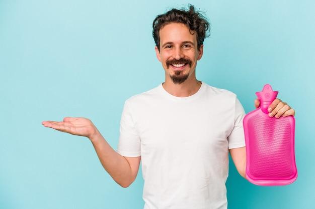 Giovane uomo caucasico che tiene una sacca d'acqua isolata su sfondo blu che mostra uno spazio di copia su un palmo e tiene un'altra mano sulla vita.
