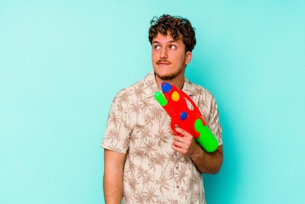 Giovane uomo caucasico in possesso di una pistola ad acqua isolata su sfondo blu che sogna di raggiungere obiettivi e scopi