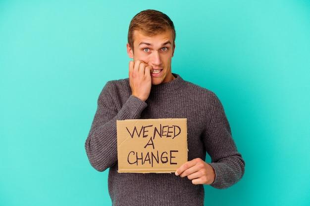 Giovane uomo caucasico che tiene un abbiamo bisogno di un cartello di cambiamento isolato su unghie mordaci blu, nervose e molto ansiose.