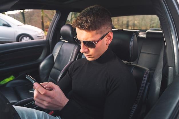 Giovane uomo caucasico all'interno di un'auto utilizzando uno smartphone