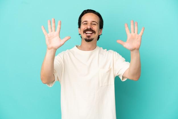 Giovane uomo caucasico isolato su sfondo blu contando dieci con le dita