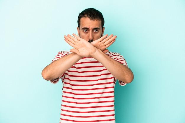 Giovane uomo caucasico isolato su sfondo blu che fa un gesto di rifiuto