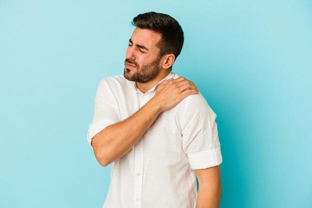 Giovane uomo caucasico isolato su sfondo blu che ha un dolore alla spalla.