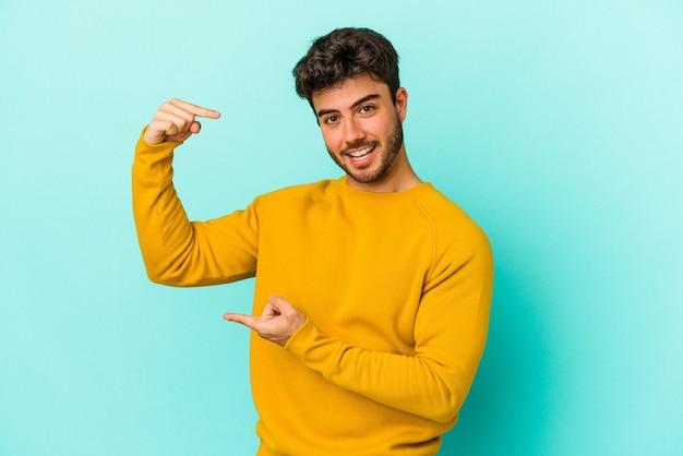 Giovane uomo caucasico isolato su sfondo blu che tiene qualcosa di piccolo con l'indice, sorridente e fiducioso.