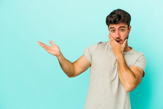 Il giovane uomo caucasico isolato su sfondo blu tiene lo spazio della copia su un palmo, tiene la mano sulla guancia. stupito e deliziato.