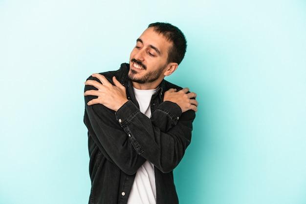 Il giovane uomo caucasico isolato sugli abbracci blu del fondo, sorride spensierato e felice.