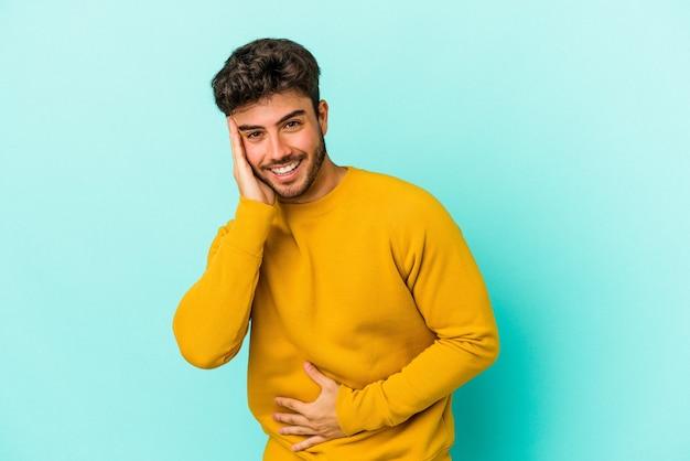 Il giovane uomo caucasico isolato su sfondo blu ride felicemente e si diverte a tenere le mani sullo stomaco.