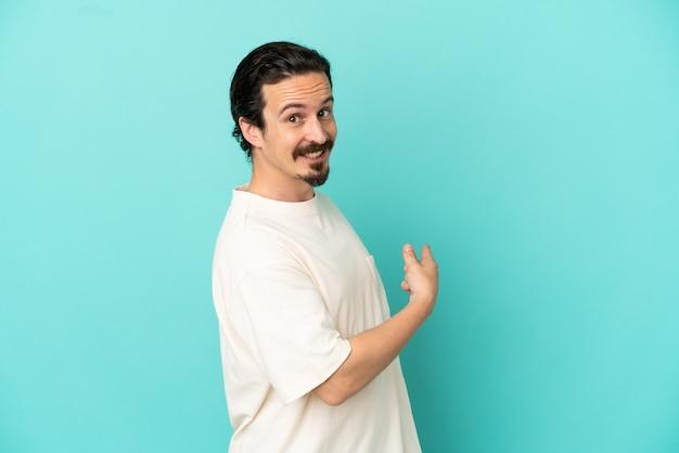 Giovane uomo caucasico isolato su sfondo blu che punta indietro