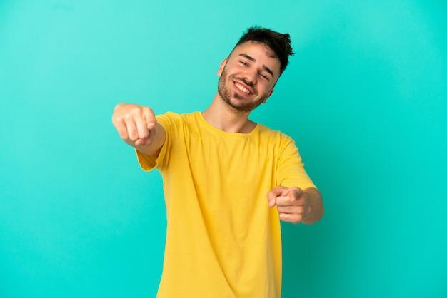 Giovane uomo caucasico isolato su sfondo blu che punta davanti con espressione felice