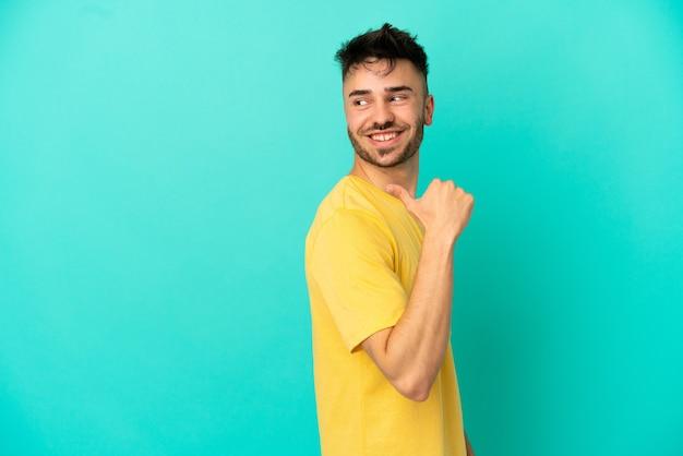 Giovane uomo caucasico isolato su sfondo blu che punta al lato per presentare un prodotto