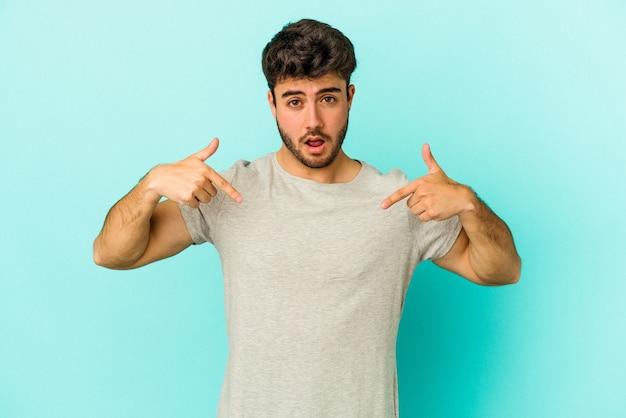 Il giovane uomo caucasico isolato su sfondo blu punta verso il basso con le dita, sensazione positiva.