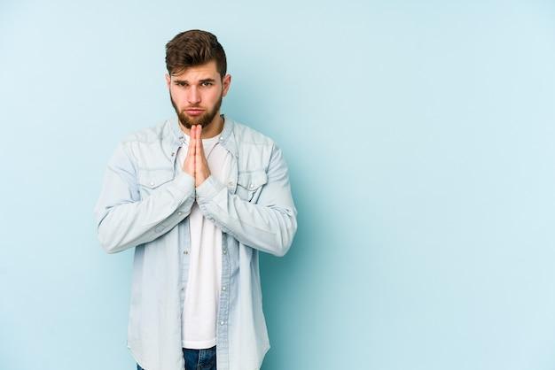 Giovane uomo caucasico isolato su sfondo blu pregando, mostrando devozione, persona religiosa in cerca di ispirazione divina.