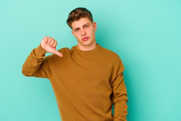 Giovane uomo caucasico isolato su sfondo blu che mostra un gesto di avversione, i pollici verso il basso. concetto di disaccordo.