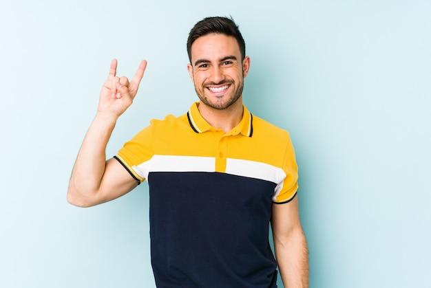 Giovane uomo caucasico isolato su sfondo blu che mostra un gesto di corna come un concetto di rivoluzione.