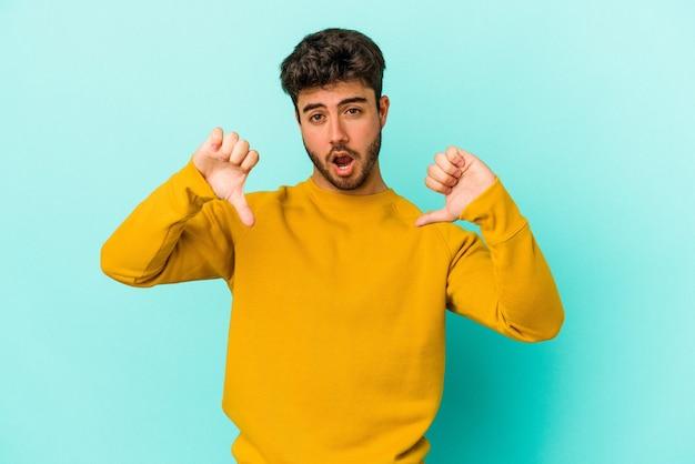 Giovane uomo caucasico isolato su sfondo blu che mostra il pollice verso il basso ed esprime antipatia.