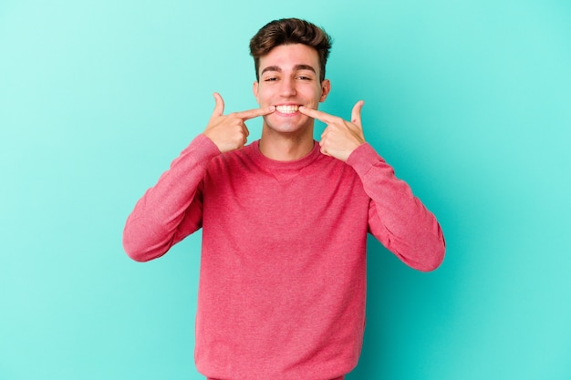 Il giovane uomo caucasico isolato su sfondo blu sorride, puntando il dito alla bocca.