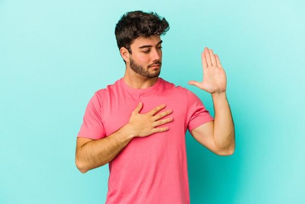 Giovane uomo caucasico isolato su sfondo blu prestando giuramento, mettendo la mano sul petto.