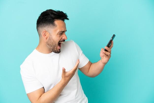 Giovane uomo caucasico isolato su sfondo blu utilizzando il telefono cellulare e cantando