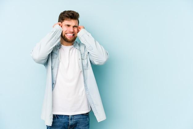 Giovane uomo caucasico isolato su blu che copre le orecchie con le mani.