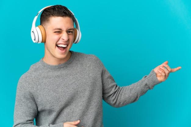 Giovane uomo caucasico isolato su musica d'ascolto blu e facendo il gesto della chitarra