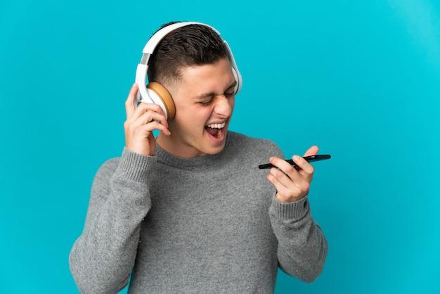 Giovane uomo caucasico isolato su musica d'ascolto blu con un cellulare e cantando