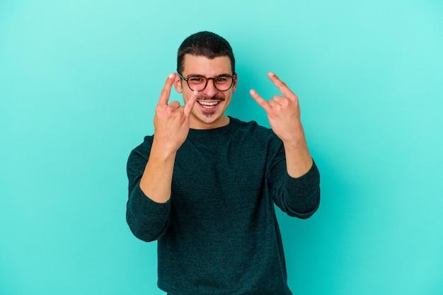 Giovane uomo caucasico isolato sul blu che mostra un gesto di corna come un concetto di rivoluzione.