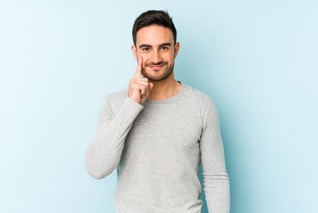 Giovane uomo caucasico isolato sul blu che mostra il numero uno con il dito.