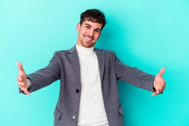 Giovane uomo caucasico isolato sull'azzurro che mostra un'espressione di benvenuto.