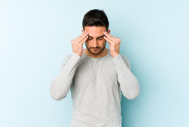 Giovane uomo caucasico isolato su blu toccando le tempie e avendo mal di testa.