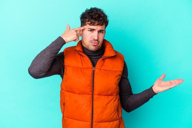 Giovane uomo caucasico isolato sulla parete blu che tiene e che mostra un prodotto a portata di mano