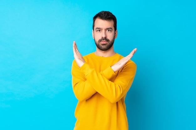Giovane uomo caucasico sopra la parete blu isolata che non fa gesto
