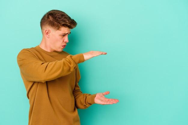Giovane uomo caucasico isolato sulla parete blu scioccato e stupito in possesso di uno spazio di copia tra le mani
