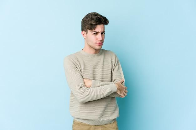 Giovane uomo caucasico isolato sulla parete blu sospettoso, incerto