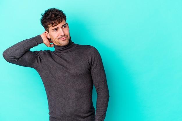 Giovane uomo caucasico isolato sulla parete blu che tocca la parte posteriore della testa, pensando e facendo una scelta