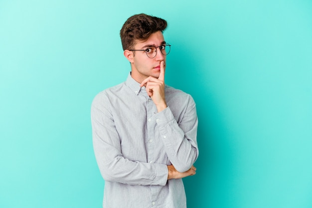 Giovane uomo caucasico isolato sulla parete blu infelice guardando a porte chiuse con espressione sarcastica